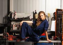 Un jeune et sexy femme posant dans un garage de véhicule photo stock