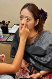Un jeune femme appliqué à elle composent par le beautician Photos stock