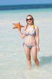 Un jeune femme avec une étoile de mer Images stock