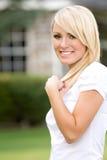 Un jeune femme blond souriant à l'extérieur Images stock