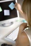 Un jeune femme collant des post-its Image libre de droits
