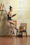 Un jeune femme dans une robe sexy affichant un livre Images stock