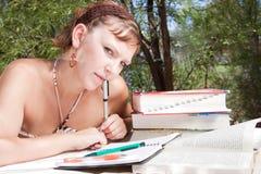 Un jeune femme pensant tout en étudiant Photo libre de droits