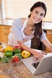 Un jeune femme recherchant une recette sur l'Internet Image libre de droits