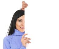 Un jeune femme se cache derrière un mur blanc Images libres de droits