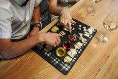 Un jeune fromage d'échantillon de couples et un vin blanc photographie stock