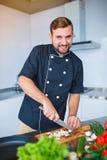 Un jeune, gai homme, coupe des champignons dans la cuisine image stock