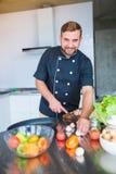 Un jeune, gai homme, coupe des champignons dans la cuisine images stock
