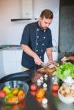 Un jeune, gai homme, coupes répand dans la cuisine, regarde la table photos libres de droits