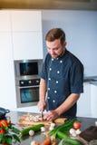 Un jeune, gai homme, coupes répand dans la cuisine, regarde la table photographie stock libre de droits