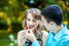 Un jeune garçon alimente la fille avec les merises Le concept est l Photos libres de droits