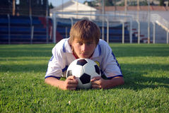 Un jeune garçon avec une bille de football photo libre de droits