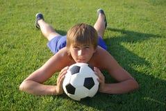 Un jeune garçon avec une bille de football image libre de droits