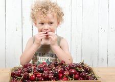 Un jeune garçon blond mangeant des cerises Photographie stock libre de droits