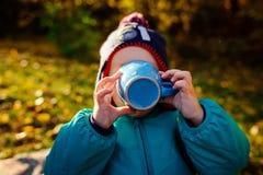 Un jeune garçon boit d'une tasse à un pique-nique images libres de droits