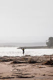 Un jeune garçon courant en bas d'une plage avec des débris de mer Images stock