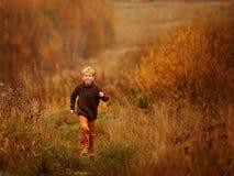 Un jeune garçon court par l'herbe d'automne Image stock