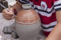 Un jeune garçon décore un pot d'argile humide Images stock