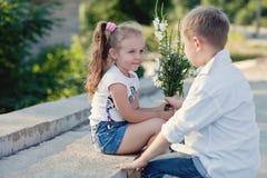 Un jeune garçon givving des fleurs au girfriend une date Photo libre de droits