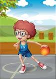 Un jeune garçon jouant le basket-ball portant un uniforme bleu Photo libre de droits