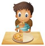 Un jeune garçon mangeant de la pizza Photos libres de droits