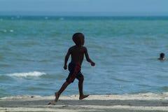 Un jeune garçon noir courant sur la plage Images libres de droits