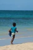 Un jeune garçon noir courant sur la plage Photographie stock libre de droits