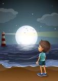 Un jeune garçon observant un fullmoon à la plage Photos stock