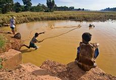 Un jeune garçon projette un filet de pêche Photos stock