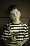 Un jeune garçon romantique avec une coiffure à la mode et une rose Photos stock
