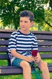 Un jeune garçon romantique avec une coiffure à la mode et une rose Image stock