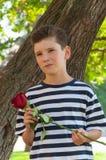 Un jeune garçon romantique avec une coiffure à la mode et une rose Images libres de droits