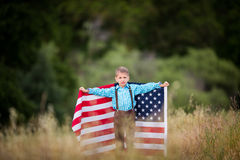Un jeune garçon tenant un grand drapeau américain, joie d'être un Américain Images stock