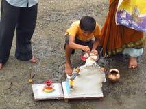 Un jeune garçon effectue le rituel traditionnel du durin de Lord Ganesh Photo stock