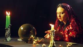 Un jeune gitan dans une robe rouge à une table par lueur d'une bougie lit l'avenir au-dessus des pierres banque de vidéos