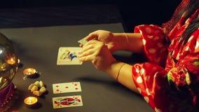 Un jeune gitan dans une robe rouge à une table par lueur d'une bougie lit l'avenir avec des cartes de fortunetelling clips vidéos