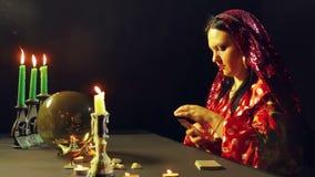 Un jeune gitan dans une robe rouge à une table par lueur d'une bougie lit l'avenir avec des cartes de fortunetelling Le plan moye banque de vidéos