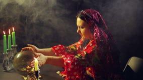 Un jeune gitan dans une robe rouge à une table par lueur d'une bougie lit l'avenir sur une boule en verre magique dans la fumée L clips vidéos