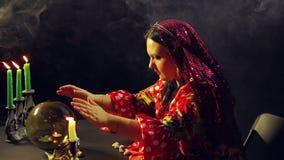 Un jeune gitan dans une robe rouge à une table par lueur d'une bougie lit l'avenir sur une boule en verre magique Le plan moyen banque de vidéos