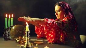 Un jeune gitan dans une robe rouge à une table par lueur d'une bougie lit l'avenir sur une boule magique Le plan moyen clips vidéos