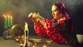 Un jeune gitan dans une robe rouge à une table par lueur d'une bougie lit l'avenir sur une boule magique Le plan moyen banque de vidéos
