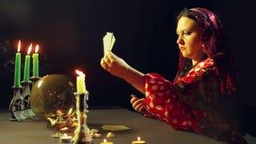 Un jeune gitan dans une robe rouge à une table par lueur d'une bougie lit l'avenir sur les cartes Le plan moyen banque de vidéos