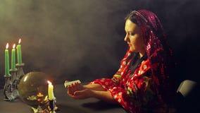 Un jeune gitan dans une salle de cartomancie par des cartes de clientèle de lueur d'une bougie pour la divination clips vidéos