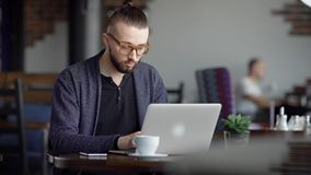 Un jeune hippie attirant dans un café, avec un intérieur moderne L'homme travaille sur son ordinateur portable élégant Un concept clips vidéos