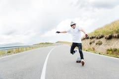 Un jeune hippie dans un casque et des gants exécutant une glissière se tenant à une grande vitesse tombe du conseil Images libres de droits