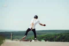 Un jeune hippie dans un casque et des gants exécutant une glissière se tenant à une grande vitesse tombe du conseil Photos stock