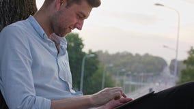 Un jeune homme à l'aide d'une Tablette dehors clips vidéos