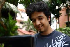 Un jeune homme à l'aide de son ordinateur portatif image libre de droits