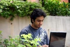 Un jeune homme à l'aide de son ordinateur portatif photographie stock