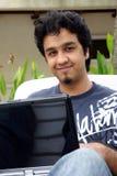 Un jeune homme à l'aide de son ordinateur portatif photos stock